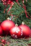 Τέσσερα κόκκινα σφαίρες Χριστουγέννων και υπόβαθρο χριστουγεννιάτικων δέντρων Στοκ φωτογραφία με δικαίωμα ελεύθερης χρήσης