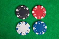 Τέσσερα μακρο τσιπ πόκερ στον πράσινο πίνακα Στοκ Εικόνες