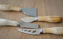 Τέσσερα μαχαίρια τυριών στο ξύλινο υπόβαθρο Στοκ εικόνες με δικαίωμα ελεύθερης χρήσης