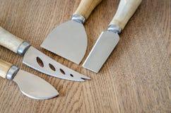 Τέσσερα μαχαίρια τυριών στο ξύλινο υπόβαθρο Στοκ Φωτογραφία