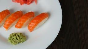 Τέσσερα μεγάλα σούσια με το κομμάτι του σολομού βρίσκονται σε ένα μεγάλο επίπεδο πιάτο Ζουμ καμερών απόθεμα βίντεο