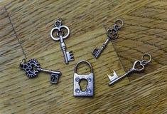 Τέσσερα μικρά διακοσμητικά κλειδιά σκελετών γύρω από ένα κλειστό παλαιό fashione στοκ φωτογραφίες