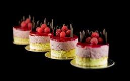 Τέσσερα μικρά κέικ με τη σοκολάτα και τα σμέουρα Στοκ εικόνες με δικαίωμα ελεύθερης χρήσης