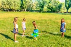 Τέσσερα μικρά κορίτσια που παίζουν τα ελαστικά στο πάρκο Στοκ φωτογραφία με δικαίωμα ελεύθερης χρήσης