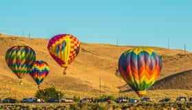 Τέσσερα μπαλόνια ζεστού αέρα κοντά στο χώρο στάθμευσης στοκ εικόνες