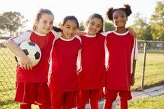 Τέσσερα νέα κορίτσια στη λουρίδα ποδοσφαίρου που κοιτάζουν στο χαμόγελο καμερών στοκ φωτογραφία