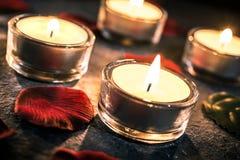 Τέσσερα ο βαλεντίνος Candlelights στην πλάκα με τα ροδαλά πέταλα και βγάζει φύλλα Στοκ Φωτογραφίες
