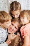 Τέσσερα παιδιά που φιλούν τη μητέρα. Οικογενειακή έννοια στοκ φωτογραφίες