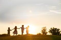 Τέσσερα παιδιά παίζουν στο ηλιοβασίλεμα Στοκ φωτογραφία με δικαίωμα ελεύθερης χρήσης