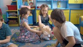 Τέσσερα παιδιά παίζουν στο πάτωμα με τα παιχνίδια φιλμ μικρού μήκους