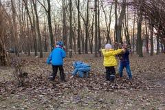 Τέσσερα παιδιά που παίζουν με το φύλλωμα περασμένου χρόνου στο πάρκο Στοκ Φωτογραφίες