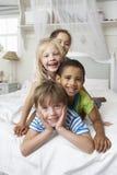 Τέσσερα παιδιά που παίζουν στο κρεβάτι από κοινού Στοκ Φωτογραφίες