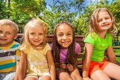 Τέσσερα παιδιά στον πάγκο στο πάρκο Στοκ φωτογραφίες με δικαίωμα ελεύθερης χρήσης