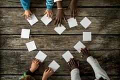 Τέσσερα παιδιά των μικτών φυλών που συγκεντρώνουν μια μορφή καρδιών του άσπρου γ Στοκ Φωτογραφία