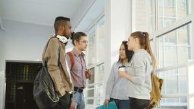Τέσσερα πολυ-εθνικά studens στέκονται στη μεγάλη άσπρη ευρύχωρη αίθουσα στο κολλέγιο που μιλά ο ένας στον άλλο με το θετικό τρόπο απόθεμα βίντεο