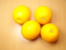 Τέσσερα πορτοκάλια στο υπόβαθρο στοκ εικόνες