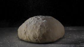 Τέσσερα που αφορούν τη φρέσκια ακατέργαστη ζύμη στο μαύρο υπόβαθρο σε σε αργή κίνηση Πλαίσιο Ο μάγειρας κοσκινίζει το αλεύρι για  απόθεμα βίντεο
