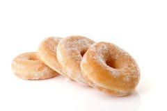 Τέσσερα που συσσωρεύονται γλυκαμένος donuts πέρα από το άσπρο υπόβαθρο στοκ φωτογραφία με δικαίωμα ελεύθερης χρήσης
