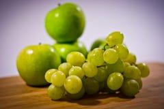 Τέσσερα πράσινα μήλα και σταφύλια Στοκ Εικόνες