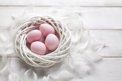 Τέσσερα ρόδινα αυγά Πάσχας στην άσπρα φωλιά και τα φτερά Στοκ εικόνα με δικαίωμα ελεύθερης χρήσης