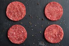 Τέσσερα φρέσκα ακατέργαστα πρωταρχικά μαύρα burger βόειου κρέατος του Angus patties Στοκ Εικόνα