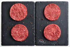 Τέσσερα φρέσκα ακατέργαστα πρωταρχικά μαύρα burger βόειου κρέατος του Angus patties Στοκ Εικόνες