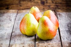 Τέσσερα φρέσκα οργανικά ώριμα αχλάδια στο αγροτικό υπόβαθρο στοκ εικόνες