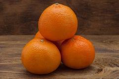Τέσσερα φωτεινά πορτοκαλιά ώριμα μανταρίνια που βάζουν μια φωτογραφική διαφάνεια Στοκ Φωτογραφίες
