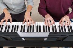 Τέσσερα χέρια που παίζουν στα κλειδιά πιάνων Στοκ φωτογραφίες με δικαίωμα ελεύθερης χρήσης