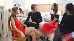 Τέσσερα όμορφα κορίτσια διοργανώνουν τις συζητήσεις κουτσομπολιού καθμένος στον καναπέ Γυναίκες που έχουν το γέλιο διασκέδασης στ απόθεμα βίντεο