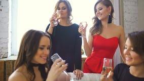 Τέσσερα όμορφα κορίτσια πίνουν τη σαμπάνια και τις ευθυμίες Γυναίκες που έχουν το γέλιο διασκέδασης στην κρεβατοκάμαρα απόθεμα βίντεο