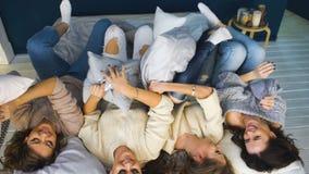 Τέσσερα όμορφα κορίτσια ρίχνουν τα μαξιλάρια μεταξύ τους Φίλες που έχουν τη διασκέδαση και το γέλιο στην κρεβατοκάμαρα απόθεμα βίντεο