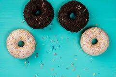 Τέσσερα donuts, σοκολάτα και με την άσπρη κρέμα, βρίσκονται σε ένα ξύλινο τυρκουάζ υπόβαθρο Στοκ Εικόνα