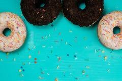 Τέσσερα donuts, σοκολάτα και με την άσπρη κρέμα, βρίσκονται semicircle σε ένα ξύλινο τυρκουάζ υπόβαθρο Στοκ φωτογραφίες με δικαίωμα ελεύθερης χρήσης