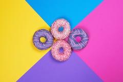 Τέσσερα donuts στο πολυ χρωματισμένο υπόβαθρο στοκ φωτογραφία