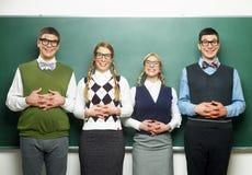 Τέσσερα nerds μπροστά από τον πίνακα Στοκ Εικόνες