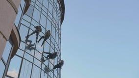 Τέσσερα steeplejacks που φορούν την εξάρτηση κρεμούν το εξωτερικό εμπορικό κέντρο απόθεμα βίντεο