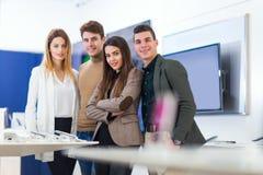 Τέσσερις άνθρωποι επιλέγουν τα έξυπνα τηλέφωνα στο κατάστημα Στοκ Εικόνες
