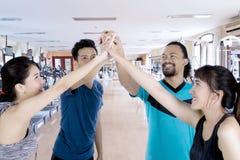 Τέσσερις άνθρωποι κάνουν την υψηλή χειρονομία πέντε χεριών Στοκ Εικόνα