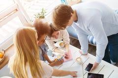 Τέσσερις άνθρωποι μελετούν και εργάζονται ομαδικά Το ξανθό κορίτσι δείχνει στο σημειωματάριο ενώ οι φίλοι της εξετάζουν Στοκ Εικόνες