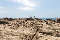 Τέσσερις άνθρωποι που αλιεύουν στους βράχους στην παραλία ξημερωμάτων Στοκ Εικόνα