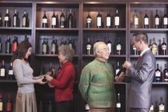 Τέσσερις άνθρωποι που εξετάζουν και που συζητούν το κρασί σε ένα κατάστημα κρασιού Στοκ Φωτογραφία