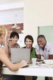 Τέσσερις άνθρωποι που διοργανώνουν τη συνεδρίαση γύρω από το γέλιο lap-top. Στοκ Φωτογραφίες