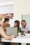 Τέσσερις άνθρωποι που διοργανώνουν τη συνεδρίαση γύρω από το lap-top. Στοκ Εικόνες
