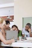 Τέσσερις άνθρωποι που διοργανώνουν τη συνεδρίαση γύρω από το lap-top. Στοκ εικόνα με δικαίωμα ελεύθερης χρήσης