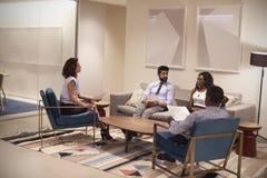 Τέσσερις άνθρωποι που συναντιούνται στον τομέα σαλονιών μιας εταιρικής επιχείρησης Στοκ φωτογραφία με δικαίωμα ελεύθερης χρήσης