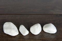Τέσσερις άσπροι βράχοι στο καφετί ξύλο Στοκ Φωτογραφία