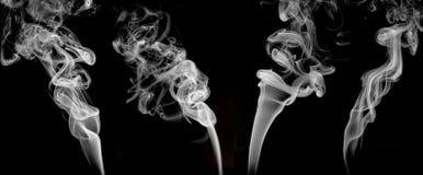 Τέσσερις άσπροι καπνοί που τίθενται στο μαύρο υπόβαθρο, γραφικός πόρος στοκ φωτογραφία