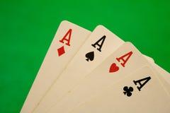 Τέσσερις άσσοι στην πράσινη τύχη τύχης παιχνιδιών χαρτοπαικτικών λεσχών υποβάθρου Στοκ Εικόνες