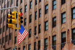 Τέσσερις αμερικανικές σημαίες που κυματίζουν στα κοντάρια σημαίας που προεξέχουν από την πλευρά να ενσωματώσει την πόλη της Νέας  Στοκ εικόνες με δικαίωμα ελεύθερης χρήσης
